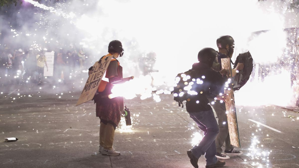 Protesters walk away from crowd control munitions launched by federal officers during a Black...
