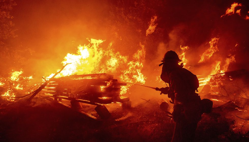 A firefighter battles the Creek Fire as it threatens homes in the Cascadel Woods neighborhood...