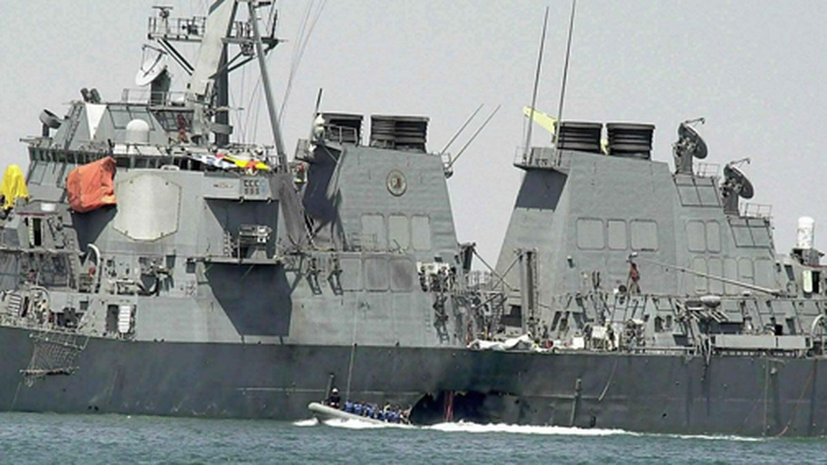 In this Oct. 15, 2000 file photo, experts in a speed boat examine the damaged hull of the USS Cole at the Yemeni port of Aden after an al-Qaida attack that killed 17 sailors. (AP Photo/Dimitri Messinis, File)