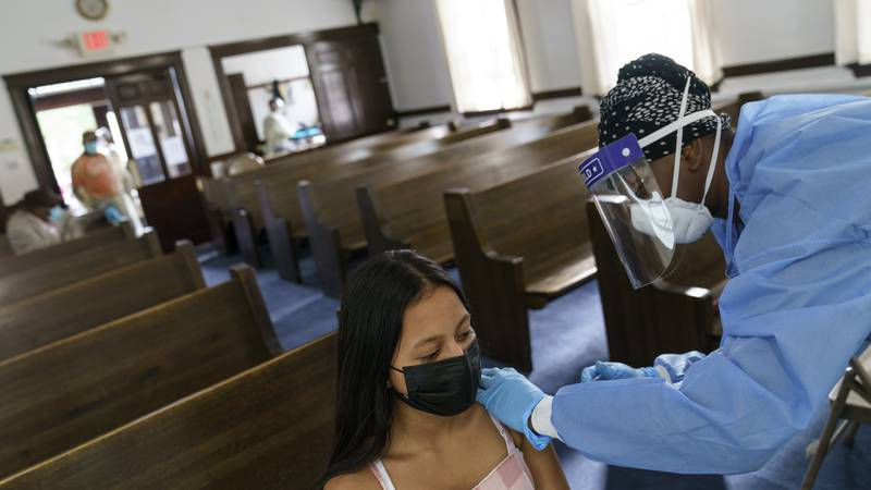 Mariana Jacome, 13, receives a COVID-19 vaccine from family nurse practitioner Temperance...