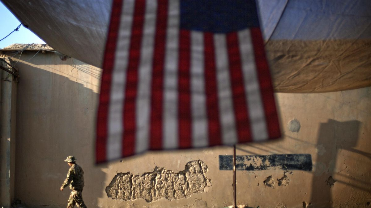 In this Sept. 11, 2011 file photo, a U.S. Army soldier walks past an American Flag hanging in...