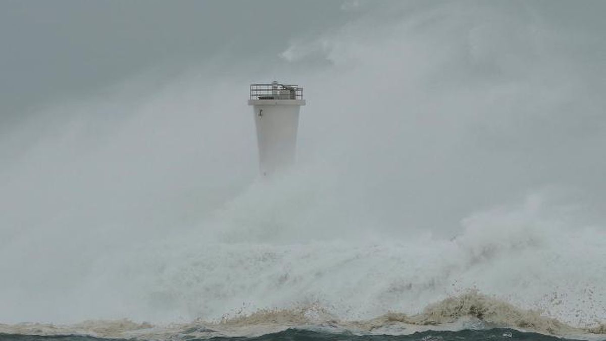 Surging waves hit against the breakwater and a lighthouse as Typhoon Hagibis approaches at a...