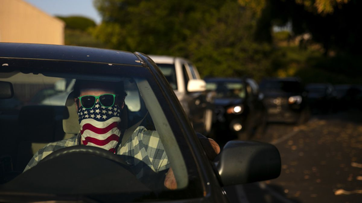 Charles McNulty wears a face covering while waiting in his car to purchase a movie ticket at Mission Tiki drive-in movie theater in Montclair, Calif., Thursday, May 28, 2020. California has relaxed its coronavirus restrictions to help the battered economy. (AP Photo/Jae C. Hong)
