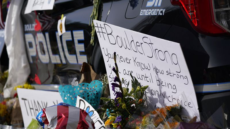 Signs, floral bouquets and tributes stand along side a police cruiser parked in front of the...