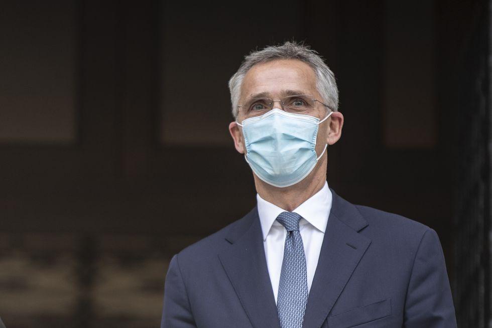 NATO Secretary-General Jens Stoltenberg, wearing a face mask stands next to Greek Prime...