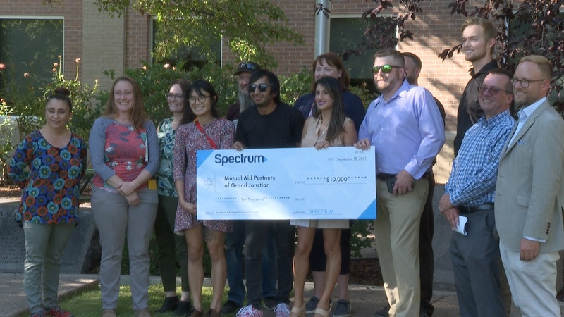 Mutual Aid Partners holding check that they received from Spectrum and Chuck McDaniel