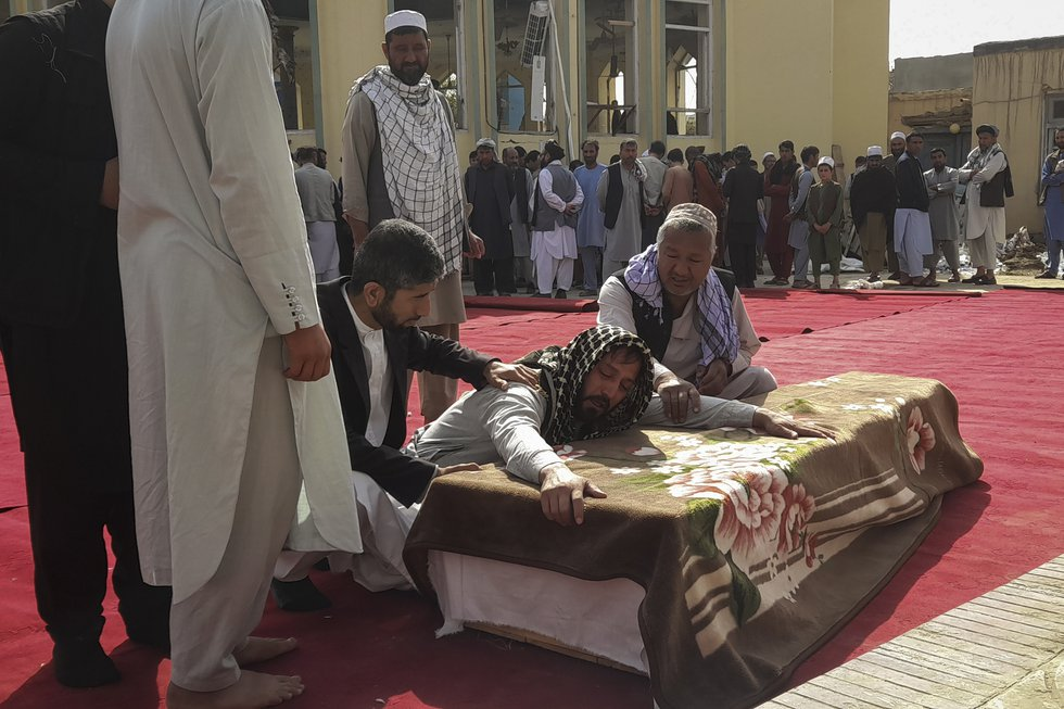 Relatives and residents attend a funeral ceremony for victims of a suicide attack at the...