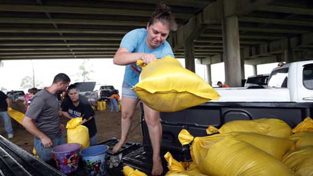Tiffany Delee tosses a filled sandbag into the back of the family truck, while her husband Mike...