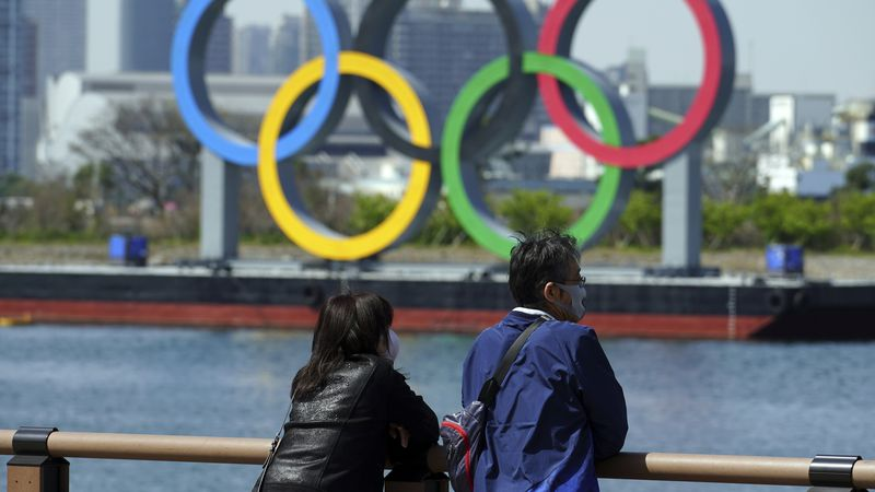 A man and a woman stand with a backdrop of the Olympic rings floating in the water in the...