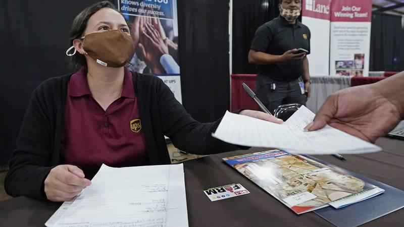 Ariel Jones, a United Parcel Service human resources intern, hands an applicant an information...